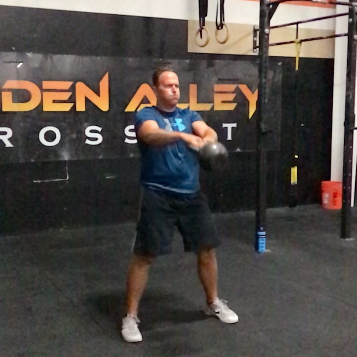 The kettlebell swing. There are two variations of a double hand kB swing: (1) the Russian KB swing and (2) the American KB swing. In this video we show the American kettlebell swing performed by Brian. This variation has a greater range of motion than the Russian kB swing. This swing goes all the way overhead, whereas the RKB ends at chest level. Without question, the American swing puts a greater demand on the shoulder joint, where the athlete performing must stabilize the kB properly once overhead. The American swing is commonly used in CrossFit for two reasons: (1) it has a longer range of motion (2) it is easier to judge a rep in competition as opposed to the Russian kB swing. If we were to argue which one is better, the answer really isn't that simple. The Russian swing can be done for a heavier load, and with a shorter range of motion, which means the posterior chain is under tension more frequently than the American swing. With that in mind the Russian kB swing is much better at building strength and muscle than the American swing. On the contrary, the American swing is an incredible tool for conditioning as it adds a muscular endurance aspect to the movement. Nonetheless, both movements are great and if done properly can be a great tool in your program. As a coach you should always assess the athletes shoulder strength and stability before performing the American swing. If your athlete has shoulder issues, modify the movement to a Russian kB swing and potentially add weight to the movement if possible